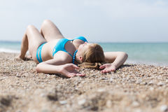 Overweight blonde sunbathing on pebble seashore Royalty Free Stock Photo