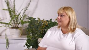 Overweight blonde woman sitting on sofa watching TV.  stock video