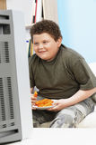 Overweight Boy With Carrot Sticks In Front Of Television Stock Image