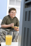 Overweight Boy Eating Bowl Of Fruit In Front Of TV stock images