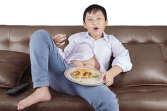 Overweight boy enjoying burger on couch Stock Photography