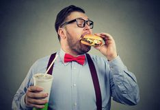 Overweight business man eating with appetite a burger holding a can of soda drink. Overweight business man eating with appetite a burger holding a big can of royalty free stock photo