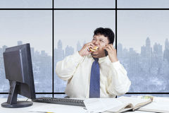 Overweight businessman eat while working. Overweight entrepreneur sitting in the office while working, eating, and talking on cellphone Stock Images