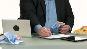 Overweight businessman eating fast food at office.