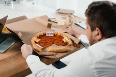 overweight businessman eating pizza at workplace stock photos