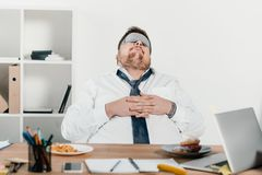 overweight businessman in sleeping mask relaxing stock photography