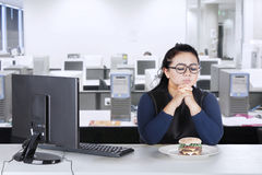 Overweight businesswoman hesitates eat burger at home Stock Images