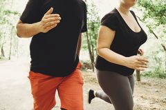 Overweight couple losing weight running together stock photo