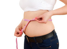 Overweight, fat  woman measuring her belly Royalty Free Stock Image