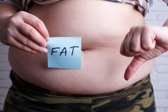 Overweight fat woman with a word Fat and thumb down. Negative em. Otions, motivation, weight losing concept Stock Photos