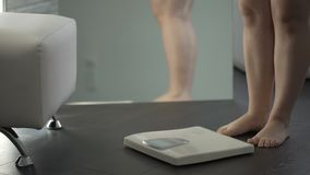 Overweight female hesitating before stepping on scales to check weight, fear