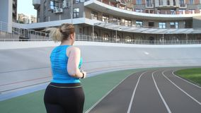 Overweight female jogging along stadium track. Close-up back view of plus size woman jogger exercising early morning on sports ground. Active fat female in stock video footage