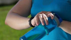 Overweight female runnner using fitness bracelet