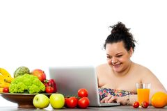 Overweight girl consulting diet on laptop. Portrait of obese teen girl searching on line for diet program.Isolated on white background royalty free stock image
