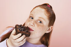 Overweight Girl Eating Brownie. Closeup portrait of an overweight girl eating brownie royalty free stock photography
