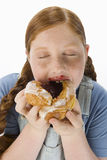 Overweight Girl Eating Pastry. Closeup of an overweight girl eating pastry against white background royalty free stock images