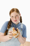 Overweight Girl Holding Pastry. Portrait of an overweight girl holding pastry against white background stock images