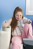 Overweight Girl With Remote Control Eats Sweet Food On Couch. Portrait of a smiling overweight girl with remote control eats sweet food on the couch Royalty Free Stock Images