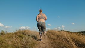 Overweight girl runs up the hill. Rear view: Overweight girl runs up the hill in the early morning. Concept of losing weight with exercise for health. Slow stock footage
