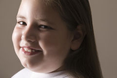 Overweight Girl Smiling. Closeup of an overweight girl smiling against gray background stock photo