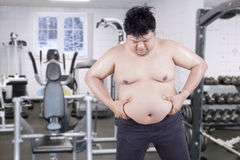 Overweight guy holds his stomach at gym Stock Photo