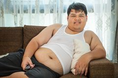 Overweight guy sitting on the couch to watch some TV. Overweight asian guy sitting on the couch with remote in hand trying to watch some TV Royalty Free Stock Photo