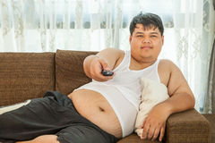 Overweight guy to watch some TV Stock Images