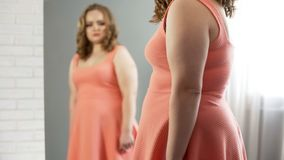 Overweight lady crying in front of mirror upset about appearance, insecurities stock images
