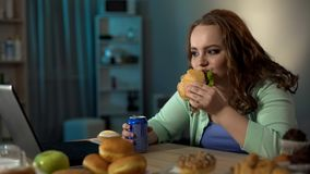 Overweight lady eating unhealthy food, watching show on laptop, sedentary life royalty free stock photography