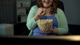 Overweight lady enjoying TV show at home, eating salty popcorn, sedentary life royalty free stock images