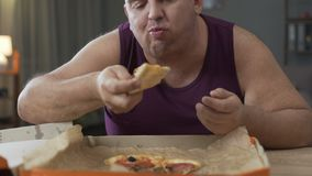 Overweight male eating pizza quickly at night time, addiction to unhealthy food. Stock footage stock video