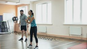 Fat man training with female instructor and doing exercises in fitness center. Thick obese guy together with personal. Overweight male and female trainer with stock footage