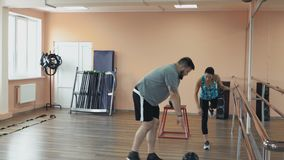 Fat man training with woman instructor and doing exercises in fitness center. Thick obese guy together with personal. Overweight male and female trainer with stock video footage