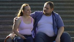 Overweight male hugging his beautiful girlfriend, resting on stairs outdoor date. Stock footage stock footage