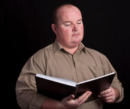 Overweight male reading from a black book Stock Photos