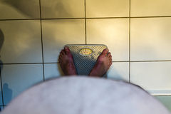 Overweight Male on Scales Royalty Free Stock Photography