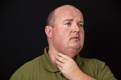 Overweight male with a sore throat. Photo of overweight male with a sore throat royalty free stock photography