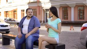 Overweight male trying to get acquainted with sporty young female on bench. Stock photo stock image