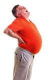 Overweight man with acute back ache bending over backwards to at Royalty Free Stock Photos
