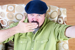 Overweight man in beret blowing kiss Stock Photography