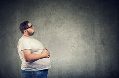 Overweight man with big belly. Overweight young man with big belly feeling full standing on gray wall background stock photo
