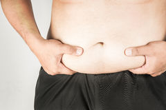 Overweight man body with hands touching belly fat Stock Photography