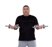 Overweight man doing fitness exercises. Overweight man with an unmotivated look is doing exercises Royalty Free Stock Images