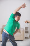 Overweight man doing some exercise at home Stock Image
