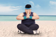 Overweight man doing yoga on beach 1 Stock Photo