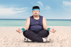 Overweight man doing yoga on beach Stock Photo