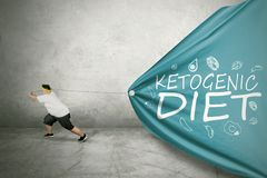 Overweight man drags Ketogenic diet text stock image