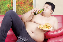 Overweight man drinking and eating on couch Royalty Free Stock Images