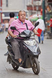 Overweight man on an e-bike, Beijing, China Stock Image