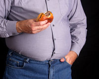 Overweight man eating a cheeseburger stock images